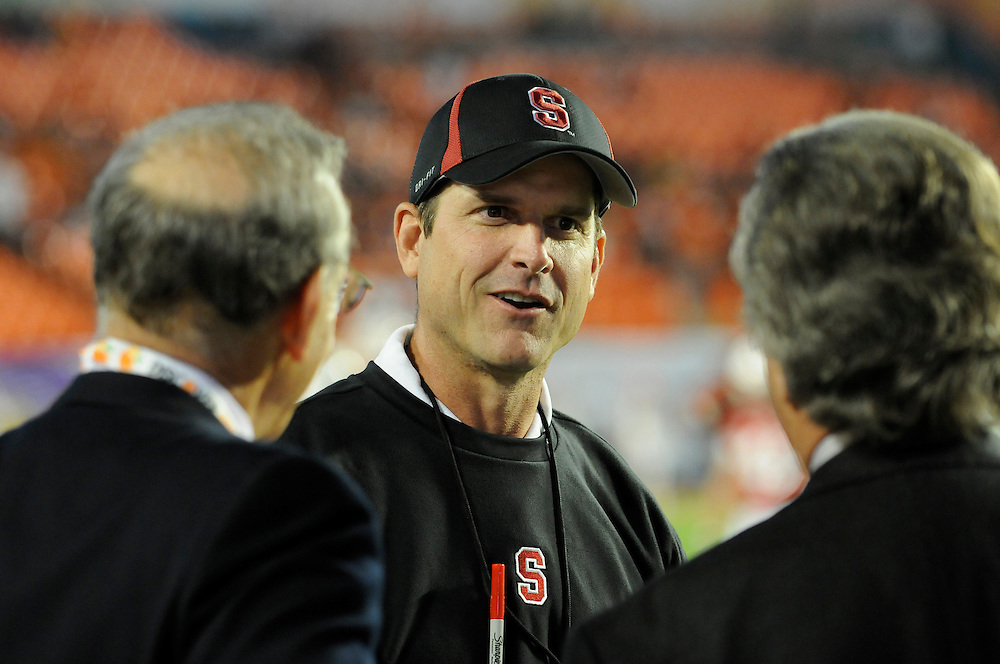 January 3, 2011: Head coach Jim Harbaugh of the Stanford Cardinal chats with Miami Dolphins owner Stephen Ross (left) and former Kansas City Chiefs general manager Carl Peterson (right) prior to the the NCAA football game between the Stanford Cardinal and the Virginia Tech Hokies at the 2011 Orange Bowl in Miami Gardens, Florida.