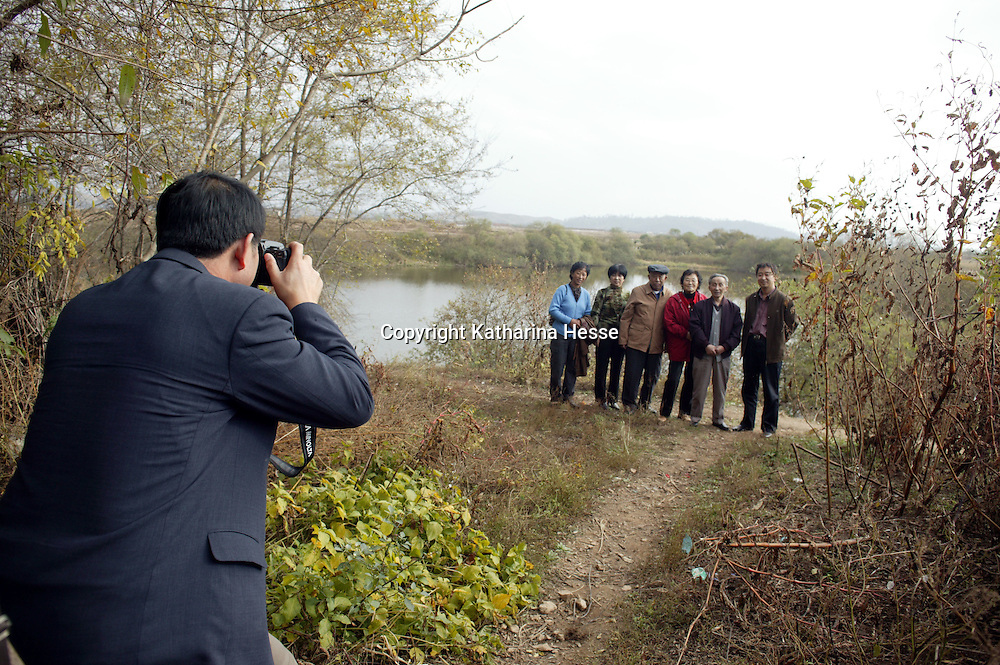 NORTHERN CHINA , OCTOBER-26:tourists take snapshots at the creek that divides China and North Korea ,October 26,2006. In some parts, the border is a small creek where people from both sides meet unofficially. As a result of the nuclear test by North Korea in early October, the border is surveilled more strictly and according to locals, meetings have become sensitive.