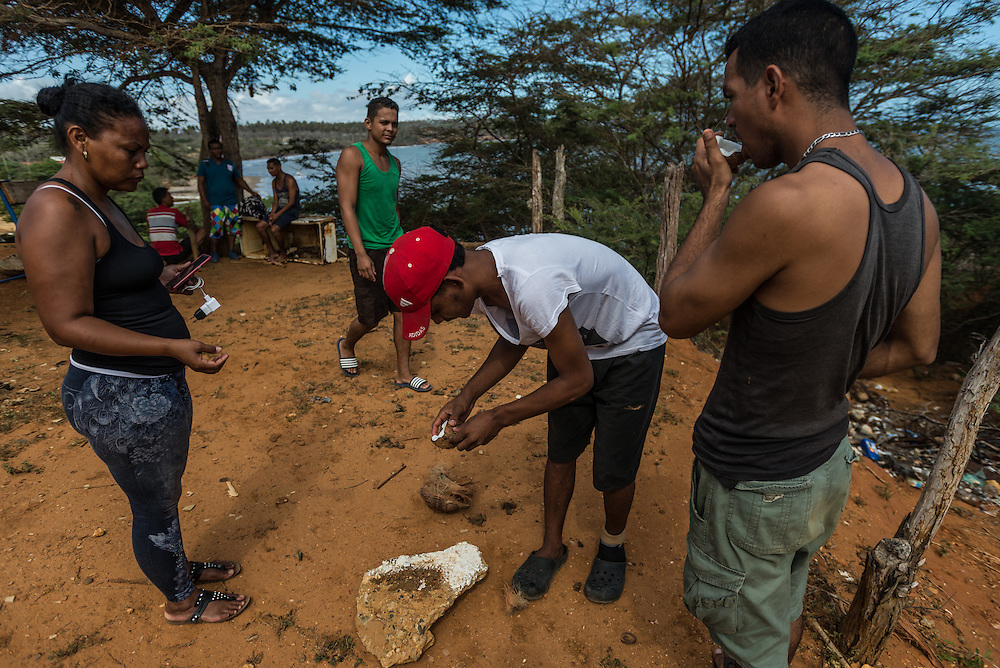 FALCÓN, VENEZUELA - SEPTEMBER 26, 2016: Undocumented migrants break open and eat scavenged coconuts as they  wait for the smuggler's boat to arrive that will illegally take them from Venezuela to Curaçao. The trip was delayed so many times, many ran out of spending money and could not afford to buy food while they waited at the smugglers safe house, so a group of men went out to find coconuts to stave off their hunger. Undocumented migrants here have mortgaged property, sold kitchen appliances and even borrowed money from the same smuggling rings that pack them on the floorboards alongside drugs and other contraband. The journey to Curaçao takes them on a 60-mile crossing filled with backbreaking swells, gangs of armed boatmen and coast guard vessels looking to capture migrants and send them home. Then, after being tossed overboard and left to swim ashore, they hide in the brush to meet contacts who spirit them anew into the tourist economy of this Caribbean island. They clean the floors of restaurants, sell trinkets on the street, or even solicit Dutch tourists for sex. But at least, the migrants say, there is food. PHOTO: Meridith Kohut for The New York Times