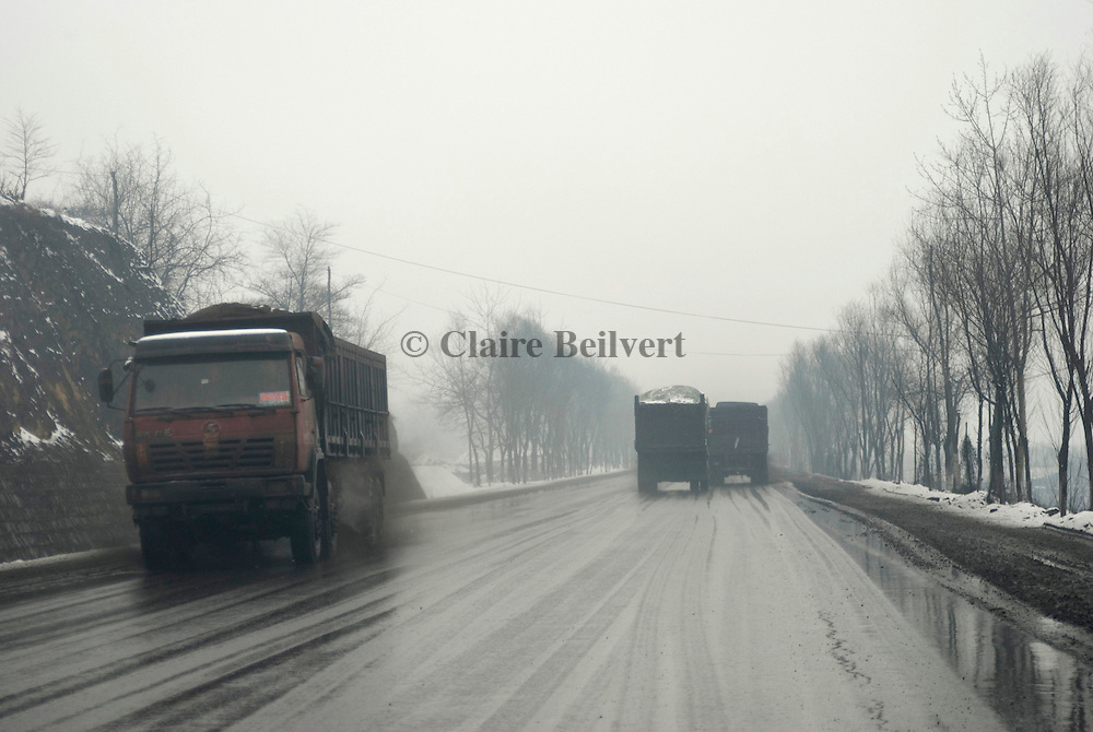 Coal trucks on a road. Days and nights hundreds of trucks are conveying coal. This Province is China's largest coal supplier with 500 millions of tonnes each year. It is also the most polluted of the country. Roads and trucks are covered with coal.