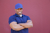 Portrait of a muscular African American delivery man with arms crossed over colored background