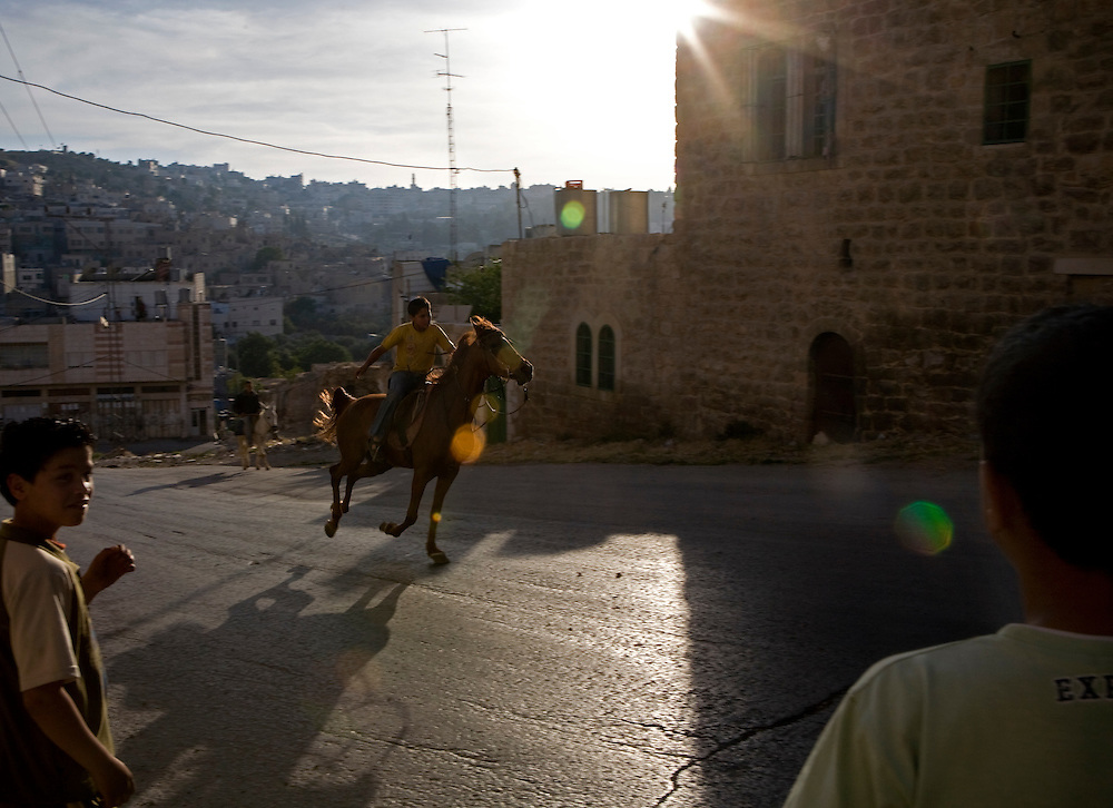 A young Palestinian boy rides a horse through an area of the West Bank city of Hebron on Tuesday 20th may 2008.