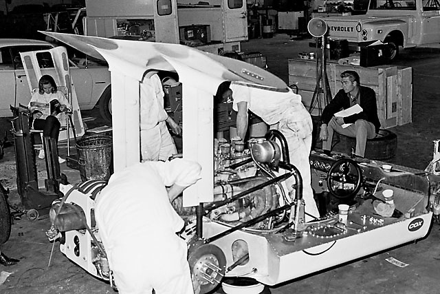 Chaparral 2G in garage at 1967 Las Vegas Can-Am.  Jim Hall sits on tire in right distance, wife Sandy Hall reads at left.