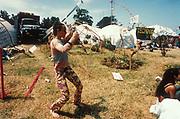 A woman twirling a baton in the Green Fields, Glastonbury Festival, UK 1995