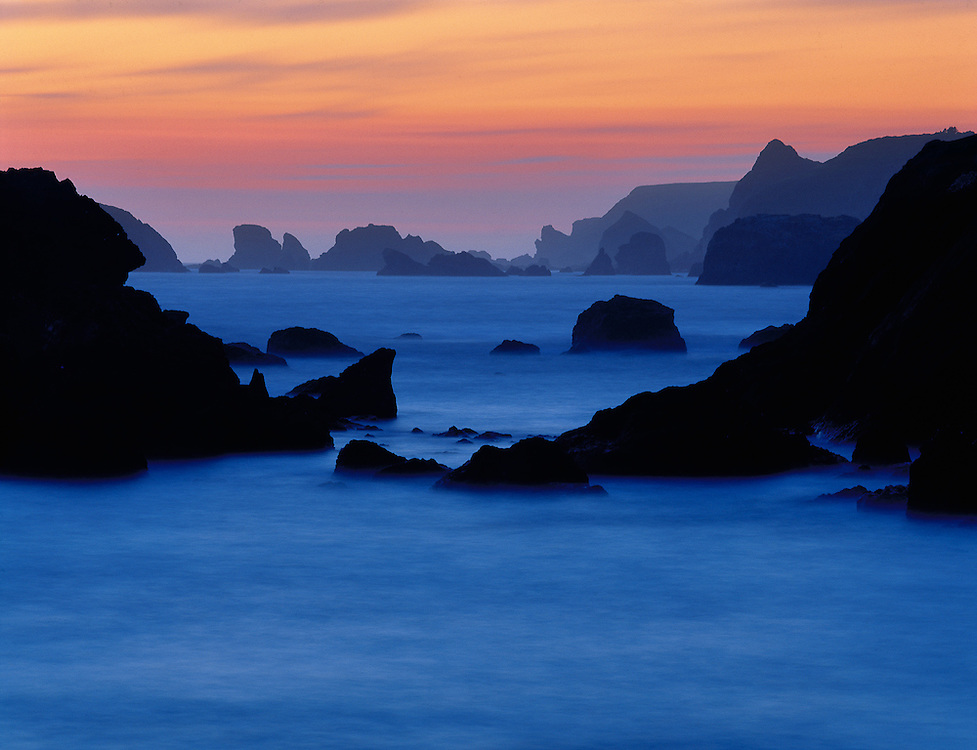 A long exposure transforms the surf into an ethereal twilight mist, at Harris Beach on the southern Oregon coast.