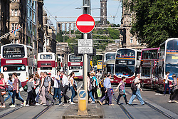 View of pedestrians crossing street and many pubic buses on Princes Street in Edinburgh , Scotland, United Kingdom
