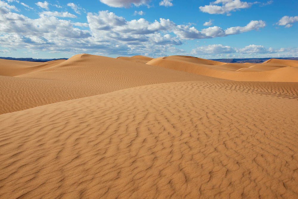 Sahara desert sand dunes with cloudy blue sky at Erg Lihoudi, M'hamid, Morocco.