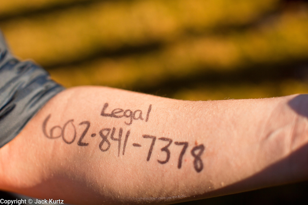 30 NOVEMBER 2011 - PHOENIX, AZ:    An anti-ALEC protester has the phone number of legal assistance written on her arm in case she is arrested in Phoenix Wednesday. About 300 people picketed the American Legislative Exchange Council (ALEC) conference at the Westin Kierland Resort and Spa in Phoenix, AZ, Wednesday. The protesters claim ALEC, a conservative think tank, violates its tax exempt status by engaging in lobbying, a charge ALEC officials deny. Many conservative pieces of legislation, like Arizona's anti-immigration bill SB1070, originate with ALEC conferences (SB 1070 originated at an ALEC conference several years ago). Many of the protesters are also members of the Occupy movement.   PHOTO BY JACK KURTZ