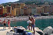 ITALY, Liguria, Camogli: vista della spiaggia.....Italy, Liguria, Camogli: reading and relaxing on the blocks.