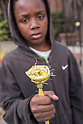 Young Gullah boy selling palmetto roses at the Historic Charleston City Market on Market Street in Charleston, SC.