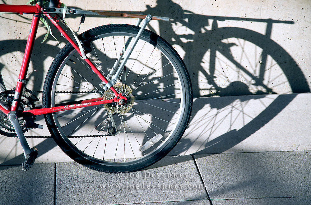 Bicycle, leaning against the concrete wall of a university building, casting dark shadows in the early morning light