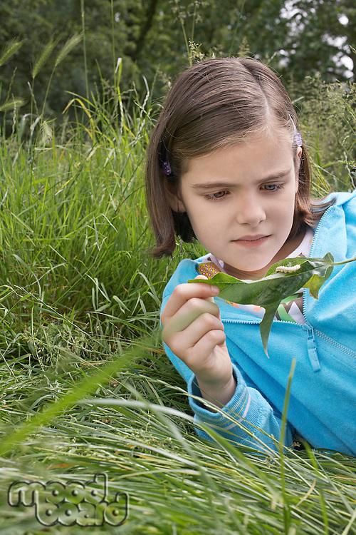 Girl (7-9) examining caterpillar on leaf in field