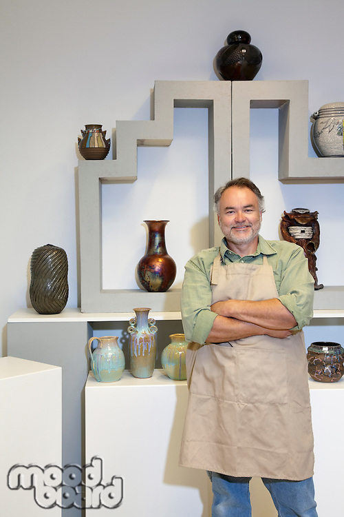 Portrait of a happy mature potter with arms crossed standing in pottery workshop