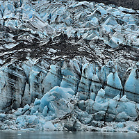 Lamplugh Glacier at Glacier Bay in Alaska<br /> This wall of ice, with its black bands or veins of moraine sediment, is the Lamplugh Glacier.  It originates about 16 miles away in the Brady Icefield within the Fairweather Range and flows about 1,000 feet a year towards the mouth of the Johns Hopkins Inlet. This blue terminus is next to Jaw Point in Glacier Bay National Park.