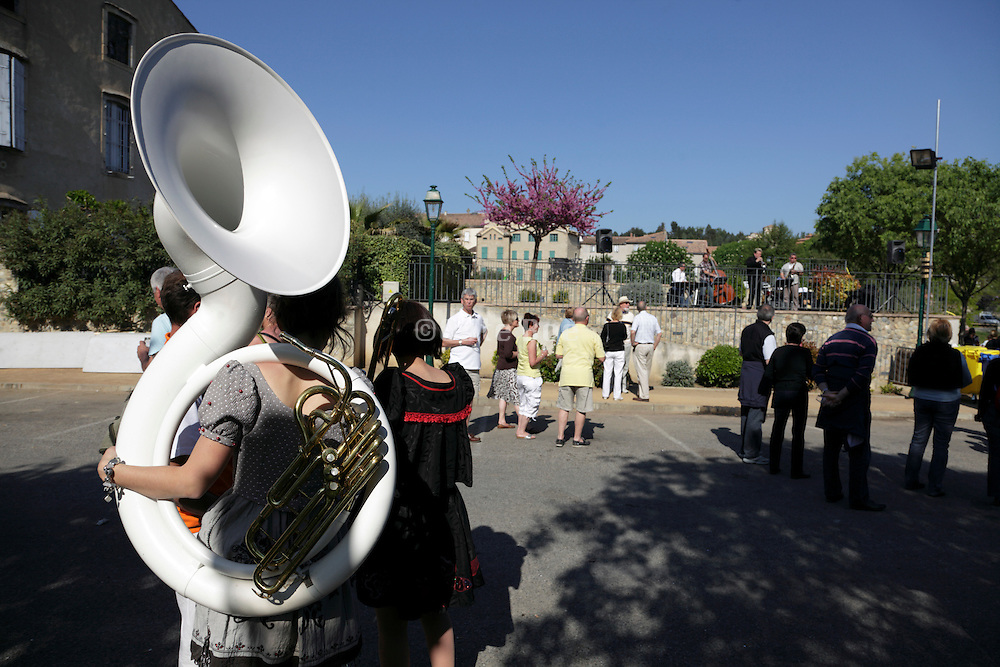 female person holding a tuba during Limoux Toque et Clocher wine festival event