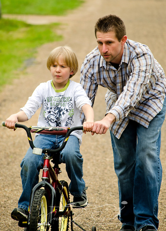 Elisha Perrigin, 6, gets help from his father, Corey Perrigin, as he rides his bicycle up a steep hill, April 21, 2012, at his father's home in New Hope, Miss. Corey Perrigin and Elisha's mother, Ashley Birckbichler, remain in close contact about Elisha, who has been diagnosed with Asperger Syndrome, a form of autism. (Photo by Carmen K. Sisson/Cloudybright)