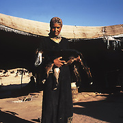 Fatima Abdullah stands by her family tent.  Her father, a bedouin from Petra prefers the traditional nomadic lifestyle working in agriculture and looking after the livestock. Fatima gets up early to prepare tea and knead the bread of the day.