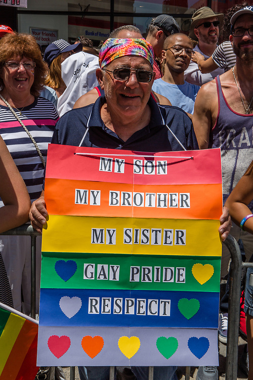 "New York, NY - 25 June 2017. New York City Heritage of Pride March filled Fifth Avenue for hours with groups from the LGBT community and it's supporters. A spectator with a rainbow sign reading "" My son / My brother / My sister / Gay Pride / Respect."""