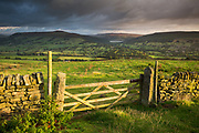 Morning light catches a gate on Shatton Moor, whilst dramatic clouds hover over the Hope and Derwent Valleys. Ladybower Reservoir can just be seen in the distance. A landscape scene in Derbyshire's Peak District, England, UK.