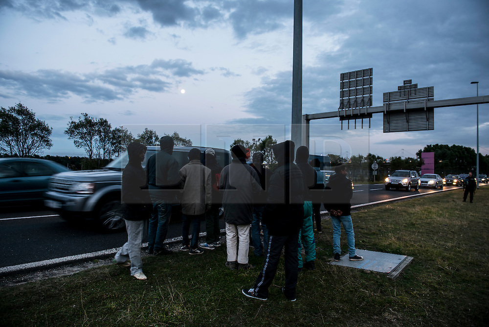 © London News Pictures. Calais, France. A group of immigrants watch cars arriving in Calais from the UK. Migrants attempting to reach the UK via the Eurotunnel at Calais in France. The situation has reached crisis point, which French police over run by attempts to cross the border. Photo credit: Ben Cawthra /LNP