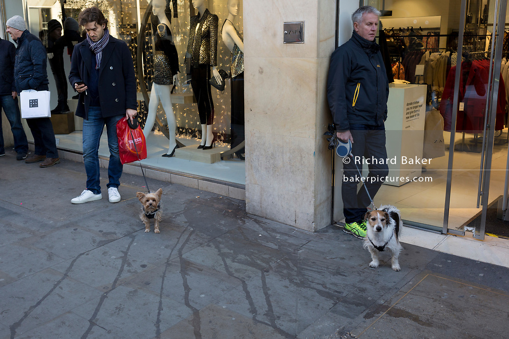 Two male dog owners wait with their pets outside a clothing retailer on Long Acre, on 27th November 2017, in London, England.