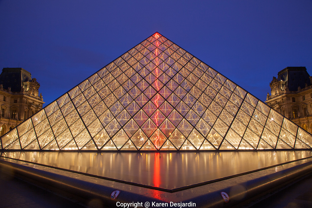 I.M. Pei's iconic Pyramid is illuminated at dusk at the Louvre museum, Paris. Visible inside the pyramid is a red, incandescent light installation by French guest artist in residence Claude Lévêque which shall remain there through January 2015. The installation is part of  Lévêque's work entitled, 'Sous la plus grand chapiteau du monde.' The red light, resembling a lightning bolt, scatters reflections to surrounding architecture. http://www.gettyimages.com/detail/photo/night-view-of-illuminated-louvre-pyramid-high-res-stock-photography/513191103