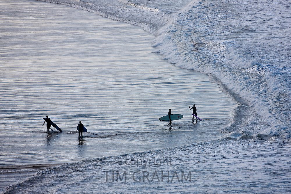 Surfers with surf boards approach waves breaking onto the beach at Woolacombe, North Devon, UK