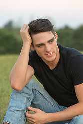 rugged good looking man with dark hair and light eyes in a black tee shirt