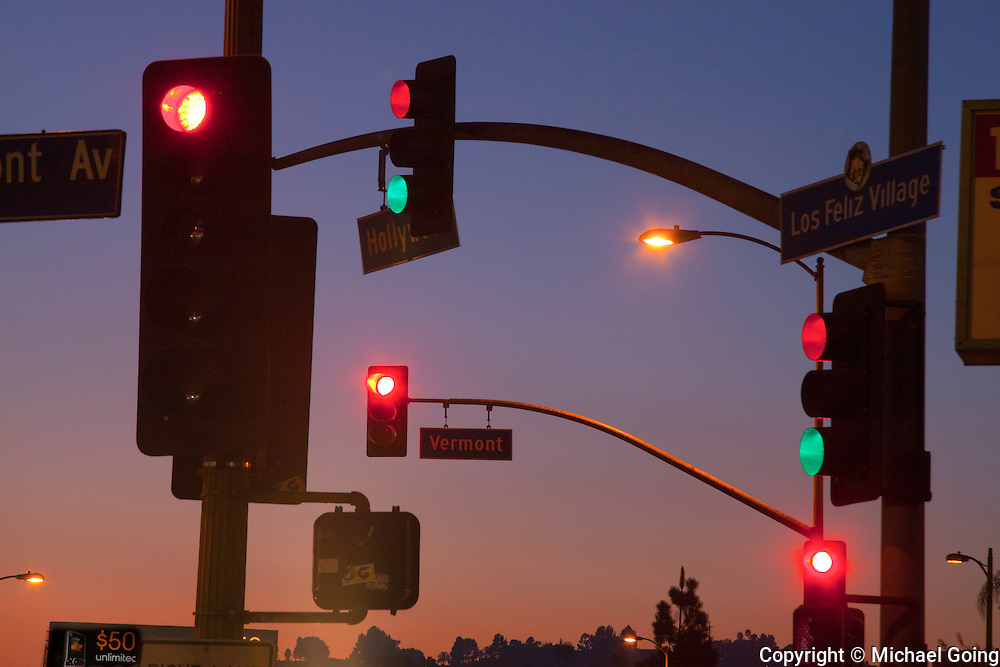 Seven traffic lights in a confusing array against twilight sunset sky in Los Angeles