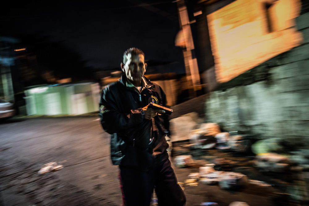 CARRIZAL, VENEZUELA - DECEMBER 10, 2016:  Police officers pursue men that ran from them, in a slum in Carrizal, Venezuela. A severe economic crisis in Venezuela, caused by the drop in oil prices and years of economic mismanagement under a Socialist government, has lead to an alarming rise in crime and insecurity in the country.  Hyperinflation has left both the working class and professional class of workers with salaries that cannot purchase enough food to feed their families. Many people are turning to crime to make ends meet.  PHOTO: Meridith Kohut for The New York Times