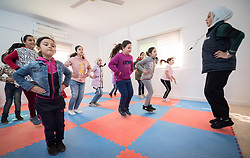 17 February 2020, Zarqa, Jordan: Incentive-Based Volunteer Lojain from Syria (right) leads a Zumba session for children at the Lutheran World Federation community centre in Zarqa. Through a variety of activities, the Lutheran World Federation community centre in Zarqa serves to offer psychosocial support and strengthen social cohesion between Syrian, Iraqi and other refugees in Jordan and their host communities.