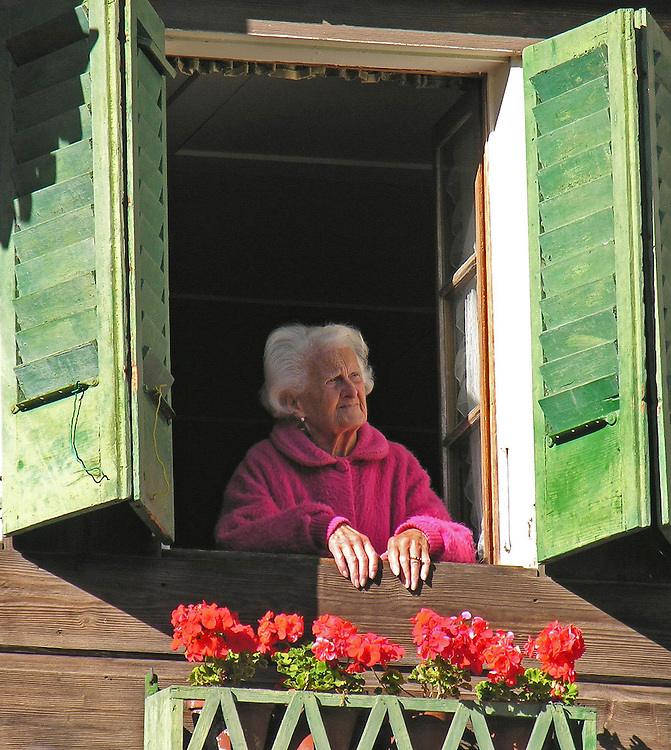 An old woman watches from her window as  people go by. Val d'Illiez, Switzerland.