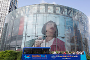 A tour bus passes a large image of a woman appearing in an ad appears on the circular structure of the IMAX cinema at Waterloo, on 15th August 2019, in London, England.