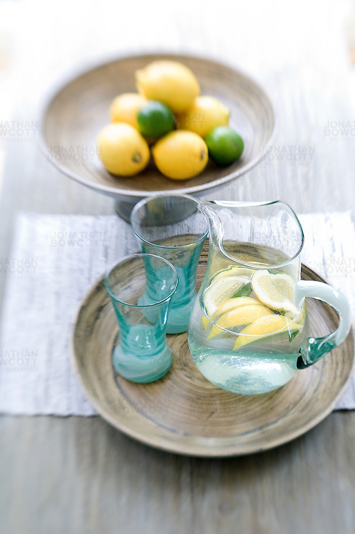 Still life photograph of refreshing jug of water with lemon
