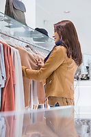 Profile shot of woman selecting sweater in store
