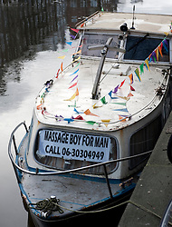 Advertisement for gay massage services on boat on canal in Amsterdam Netherlands