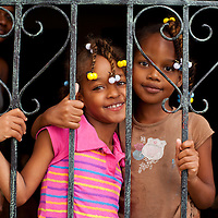 Dominican Republic, Santo Domingo, Portrait of young girls in doorway in home within Ciudad Colonial neighborhood