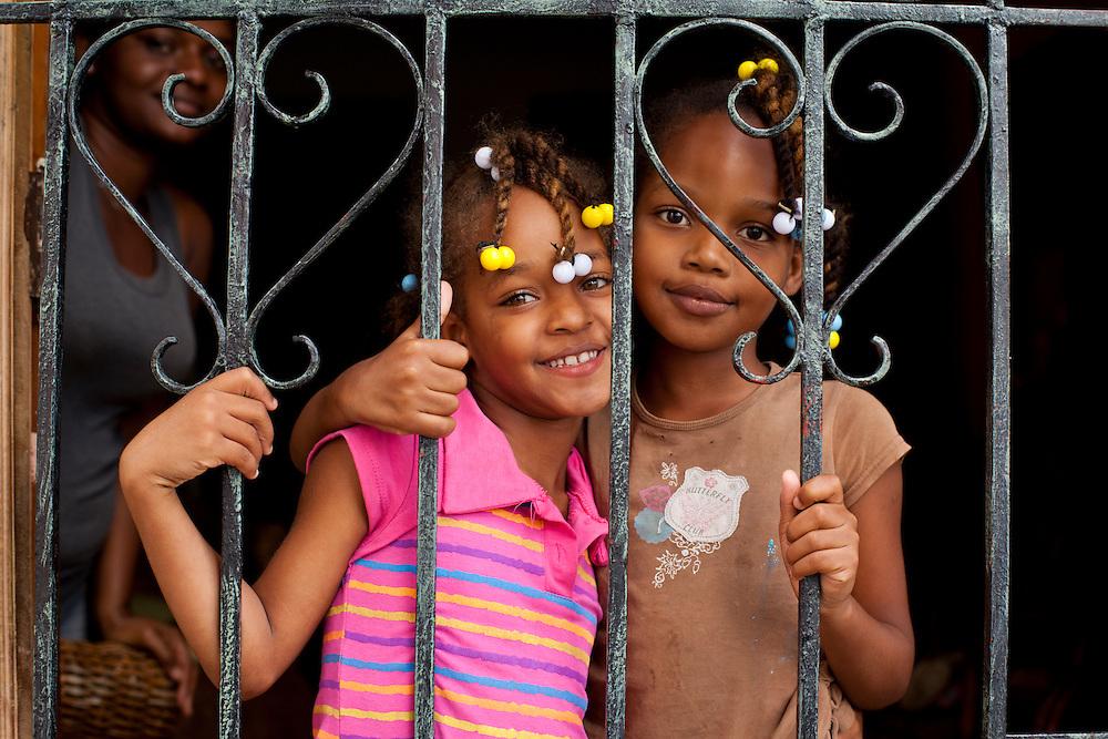 Dominican Republic, Santo Domingo, Portrait of young girls in doorway in home within Ciudad Colonial neighborhood