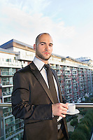 Portrait of confident businessman having cup of tea