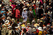 An aerial view of crowds of racegoers on Ladies Day at Royal Ascot racing week. Top-hatted gentlemen and women in posh frocks gather before the next race, planning which horses to back. Royal Ascot is held every June and is one of the main dates on the sporting calendar and English social season. Over 300,000 people make the annual visit to Berkshire during Royal Ascot week, making this Europe's best-attended race meeting. There are sixteen group races on offer, with at least one Group One event on each of the five days. The Gold Cup is on Ladies' Day on the Thursday. There is over £3 million of prize money on offer.