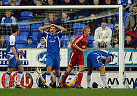Photo: Paul Greenwood.<br />Wigan Athletic v Liverpool. The Barclays Premiership. 02/12/2006. Liverpool's Dirk Kuyt (red) scores as Wigan's Matt Jackson, left and Pasul Scharner. right, react
