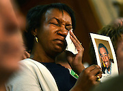 Carolun Murray cries as she holds a photo of her deceased son Justin, 19, who was a victim of gun violence, during President Barack Obama's State of the Union address in Washington, D.C.