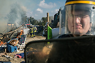 Calais, Pas-de-Calais, France - 25.10.2016    <br />  <br /> In the time after the beginning of the camp destruction numerous fires were placed in the camp. Police forces secure the work of the firefighter. 2nd day of the eviction on the so called &rdquo;Jungle&quot; refugee camp on the outskirts of the French city of Calais. Many thousands of migrants and refugees are waiting in some cases for years in the port city in the hope of being able to cross the English Channel to Britain. French authorities announced a week ago that they will evict the camp where currently up to up to 10,000 people live.<br /> <br /> In der Zeit nach dem beginn der Camp zerst&ouml;rung wurden zahlreiche Feuer im Camp gelegt. Polizisten sichern die Arbeit der Feuerwehr ab. Zweiter Tag der Raeumung des so genannte &rdquo;Jungle&rdquo;-Fluechtlingscamp in der franz&ouml;sischen Hafenstadt Calais. Viele tausend Migranten und Fluechtlinge harren teilweise seit Jahren in der Hafenstadt aus in der Hoffnung den Aermelkanal nach Gro&szlig;britannien ueberqueren zu koennen. Die franzoesischen Behoerden kuendigten vor einigen Wochen an, dass sie das Camp, indem derzeit bis zu bis zu 10.000 Menschen leben raeumen werden. <br /> <br /> Photo: Bjoern Kietzmann
