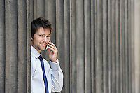 Businessman between pillars outside building talking on phone portrait