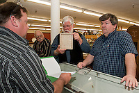Paul Kelley of Rumney presents a letter referencing land plots in Lancaster, NH that has signatures by Matthew Thornton and John Tolford (1767) and Governor Wentworth (1766)  to Linc Fournier, Doug McGowan and Bruce Baier during Laconia Historical Society's Appraisal Night at the Laconia Antique Center Tuesday evening.  (Karen Bobotas/for the Laconia Daily Sun)