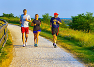 Merrick, New York, U.S. 20th June 2013. Three runners run on path around hill, at dusk on last full day of spring, at Levy Park and Preserve, the highest point of South Shore of Nassau County, Long Island.
