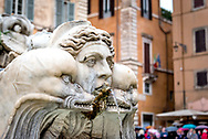 Face of a Triton with two dolphins in Fontana del Moro / Moor Fountain at Piazza Navona, Rome, Italy, with colorful tourist umbrellas and orange walls in background.