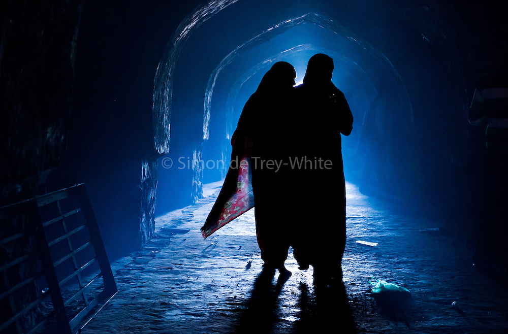 26th November 2015, New Delhi, India.  Women silhouetted in catacombs of the ruins of Feroz Shah Kotla in New Delhi, India on the 26th November 2015<br /> <br /> PHOTOGRAPH BY AND COPYRIGHT OF SIMON DE TREY-WHITE a photographer in delhi<br /> + 91 98103 99809. Email: simon@simondetreywhite.com<br /> <br /> People have been coming to Firoz Shah Kotla to pray to and leave written notes and offerings for Djinns in the hopes of getting wishes granted since the late 1970's. Jinn, jann or djinn are supernatural creatures in Islamic mythology as well as pre-Islamic Arabian mythology. They are mentioned frequently in the Quran  and other Islamic texts and inhabit an unseen world called Djinnestan. In Islamic theology jinn are said to be creatures with free will, made from smokeless fire by Allah as humans were made of clay, among other things. According to the Quran, jinn have free will, and Iblīs abused this freedom in front of Allah by refusing to bow to Adam when Allah ordered angels and jinn to do so. For disobeying Allah, Iblīs was expelled from Paradise and called &quot;Shayṭān&quot; (Satan).They are usually invisible to humans, but humans do appear clearly to jinn, as they can possess them. Like humans, jinn will also be judged on the Day of Judgment and will be sent to Paradise or Hell according to their deeds. Feroz Shah Tughlaq (r. 1351&ndash;88), the Sultan of Delhi, established the fortified city of Ferozabad in 1354, as the new capital of the Delhi Sultanate, and included in it the site of the present Feroz Shah Kotla. Kotla literally means fortress or citadel.