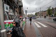Een vrouw passeert in de regen een bouwplaats op het Rokin in Amsterdam.<br /> <br /> A woman passes a construction area at the Rokin in Amsterdam.