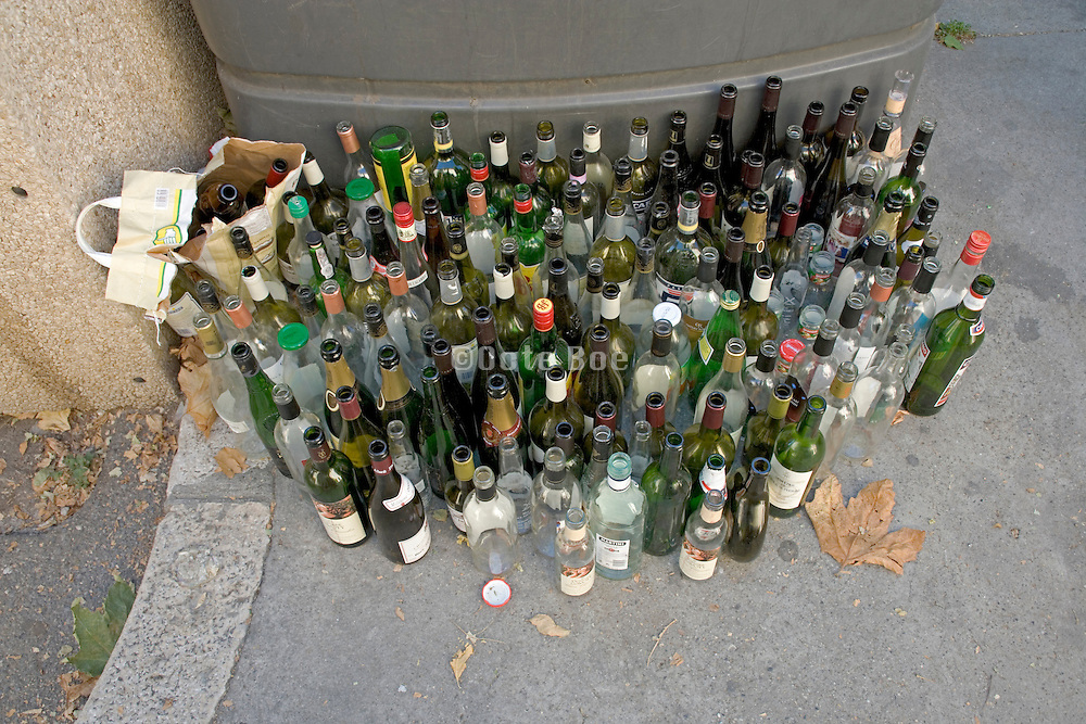 empty glass bottles placed by a recycle container